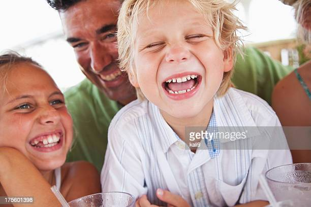 Little boy laughing with family
