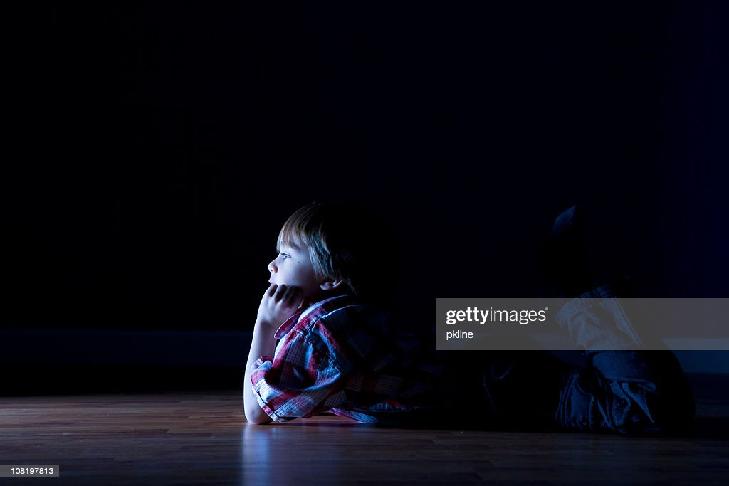 Little boy lays on the floor watching tv : Stock Photo
