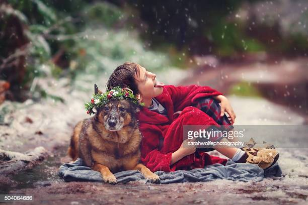 little boy leaning against dog in a snowy forest