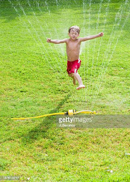 Little Boy Leaping in a Sprinkler