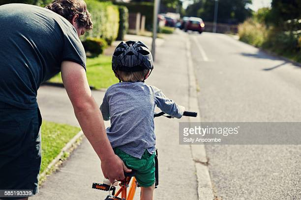 Little boy learning to ride a bicycle