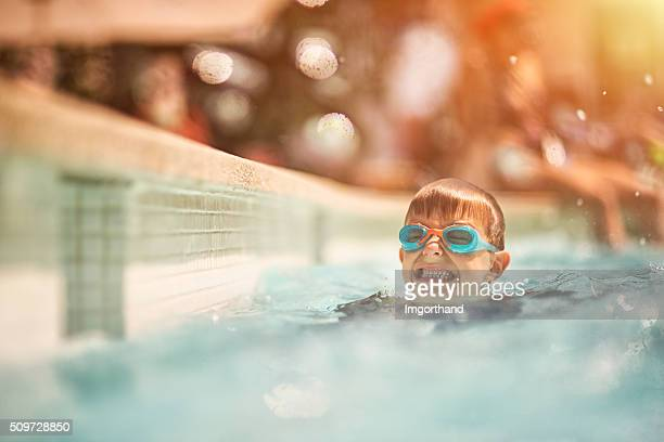 Little boy learning to swim in swimming pool