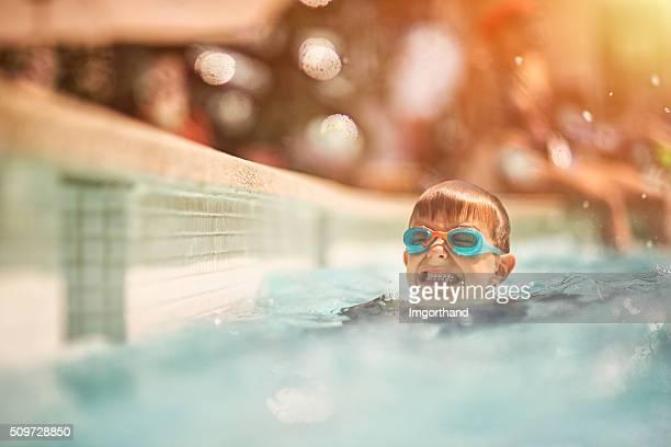 Kleiner Junge lernen, schwimmen Sie im Swimmingpool