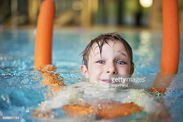 Petit garçon apprentissage se baigner avec piscine à nouilles