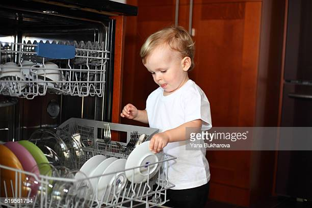 Little boy loading plates into the dishwasher