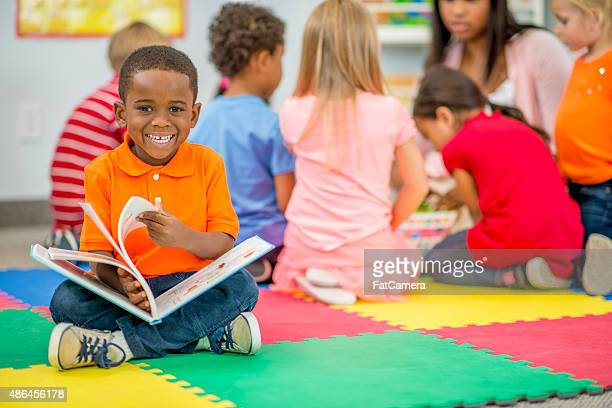 Kleiner Junge schaut Bilderbuch im Vorschulalter
