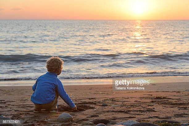 Little boy looking at sunset over sea