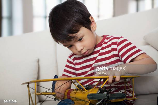 Little boy looking down and holding a model airplane,  on the couch in the living room