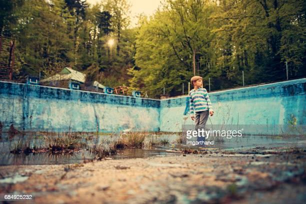 Kleiner Junge Frösche in einem verlassenen Schwimmbad suchen