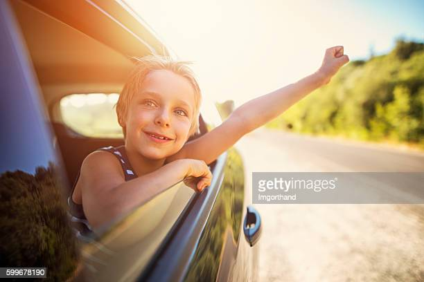 Little boy looking out of car on a road trip