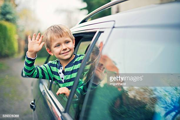 Little boy looking out of the car window and waving