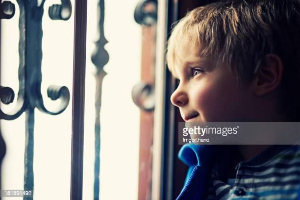 Petit garçon regardant par la fenêtre