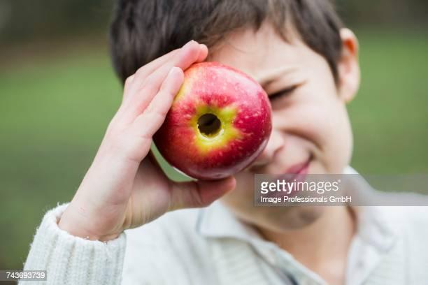 A little boy looking through a cored apple