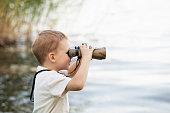 Portrait of little boy looking through binoculars on river bank. Cute kid with binoculars sitting on the pier on river