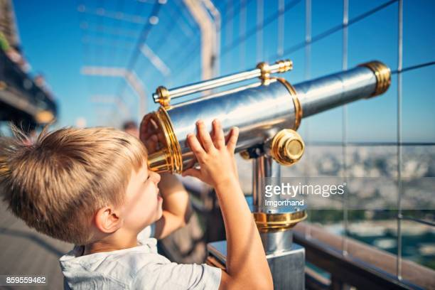 Little boy looking through coin telescope on the Eiffel Tower