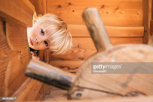 Little boy looking through hole in wooden ship on playground