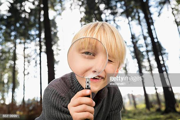 Little boy looking through magnifying glass at viewer