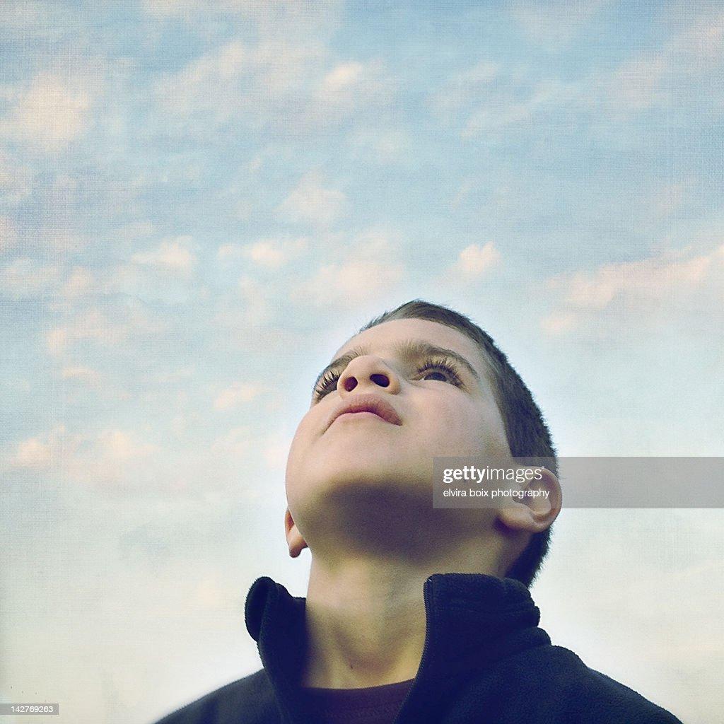 Little boy looking up in sky