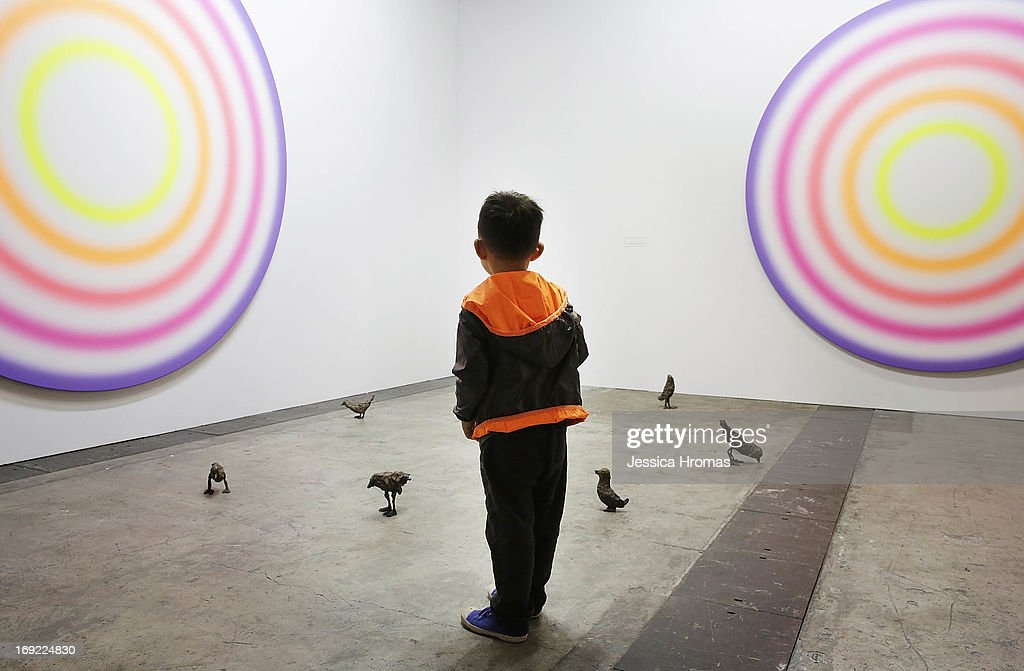A little boy looks at art works on the floor and wall by Ugo Rondinone, which are represented by gallery Galerie Eva Presenhuber at Art Basel, May 22, 2013 in Hong Kong.
