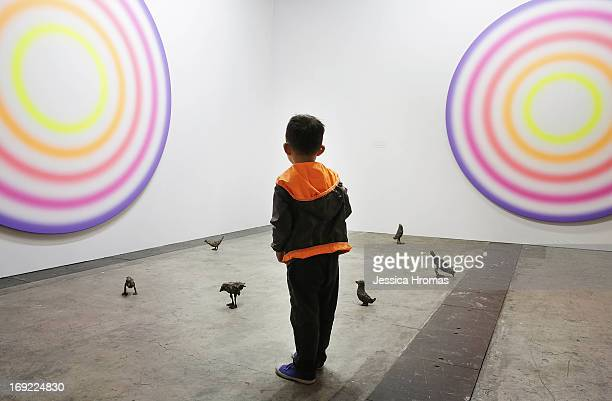 A little boy looks at art works on the floor and wall by Ugo Rondinone which are represented by gallery Galerie Eva Presenhuber at Art Basel May 22...