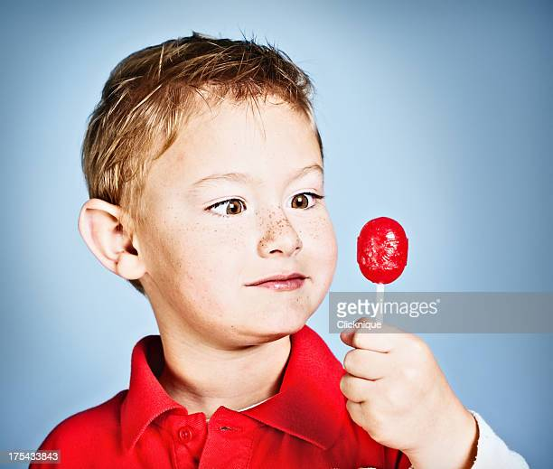 Little boy looks at sugary red lollipop considering it seriously