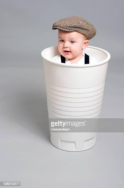 Kleine Junge sieht sich von einem gigant Kunststoff Becher