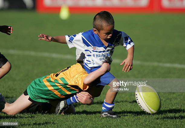 A little boy loses the ball as he gets tackled during a kids game of league in between the New Zealand Warriors v Brisbane Broncos at Ericsson...