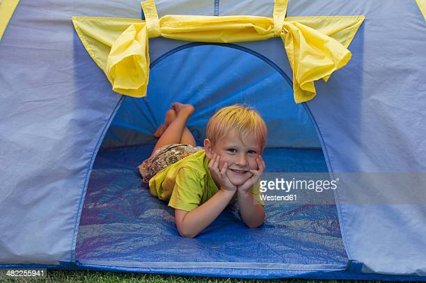 Little boy lying in a blue tent