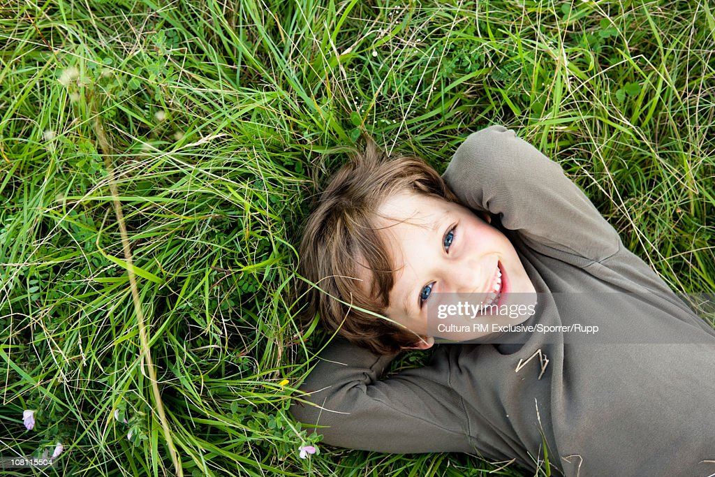 Little boy lying in grass : Stock Photo