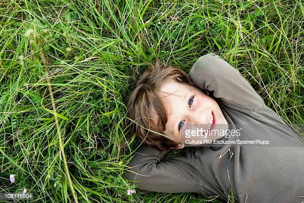 Little boy lying in grass