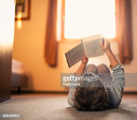 Little boy lying on back and reading a book