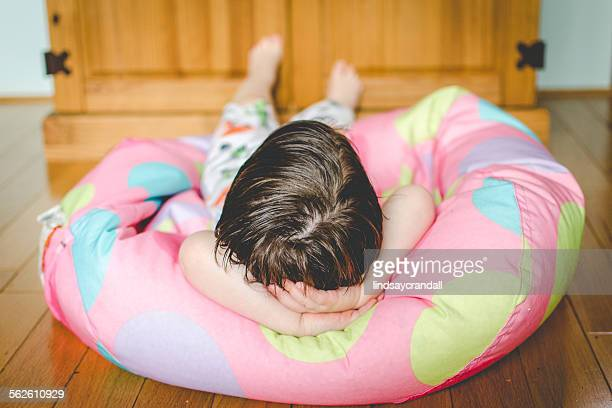 Little boy lying on bean bag chair with hands behind his head