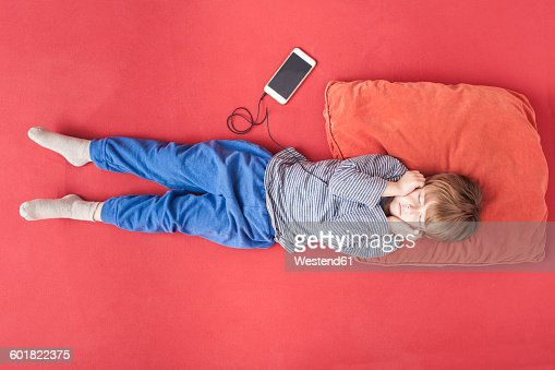 Little Boy Lying On Bed Hearing Music With Smartphone And