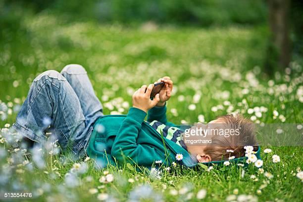 Kleine Junge liegt auf Gras, Spielen auf dem smartphone