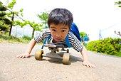 Little boy lying on skateboard