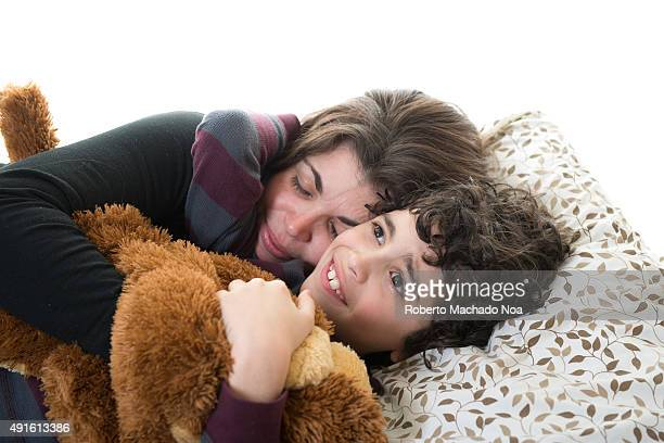Little boy lying on the bed holding his mother tightly with one hand and a soft toy with the other hand against white background The boys seems...