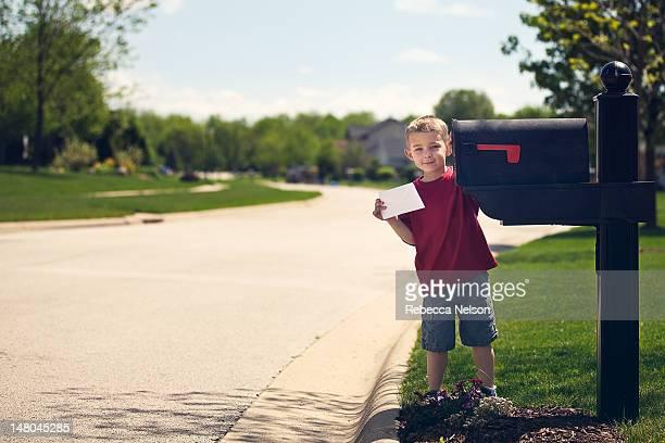 Little boy mailing letter