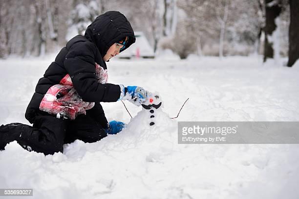 Little boy makes a snowman in winter