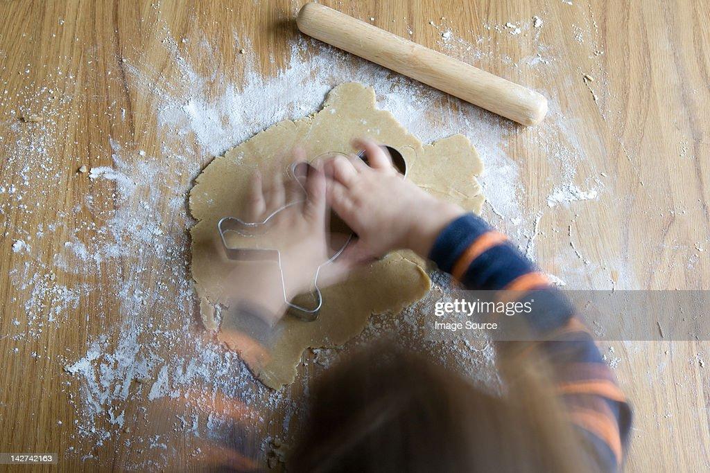 Little boy making gingerbread men : Stock Photo