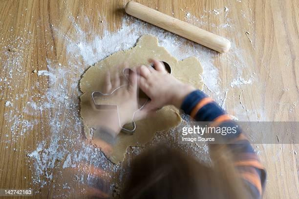 Piccolo ragazzo facendo uomo di pan di zenzero