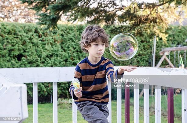 Petit garçon fait de bulles de savon et essayer de les tenir pour