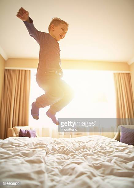 Little boy mid air jumping with joy on bed.