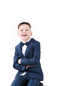 Adorable cheerful handsome boy posing in modern kids suit with big sincere smile on his face, Isolated on white background