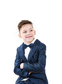 Charming little boy model posing with his arms crossed in suit wih bowtie and smiling, Isolated on white background