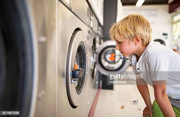 Little boy observing working laundromat in self-service laundry