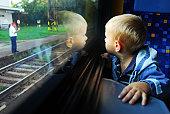 Little boy looking through window. He travels on a train.