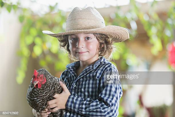 Little boy on farm holding a chicken