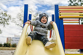 Close Up portrait of Boy Sliding down the slide in Park in Autumn day. Cold, Winter, smiling, having fun