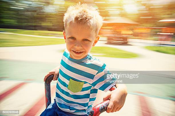 Petit garçon sur le terrain de jeu de spinning sur carousel