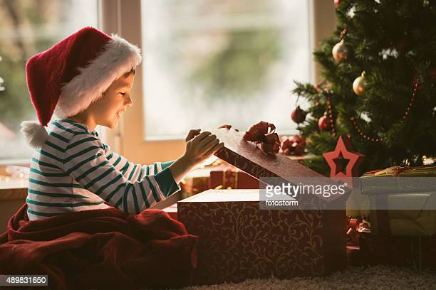 Little boy opening Christmas present